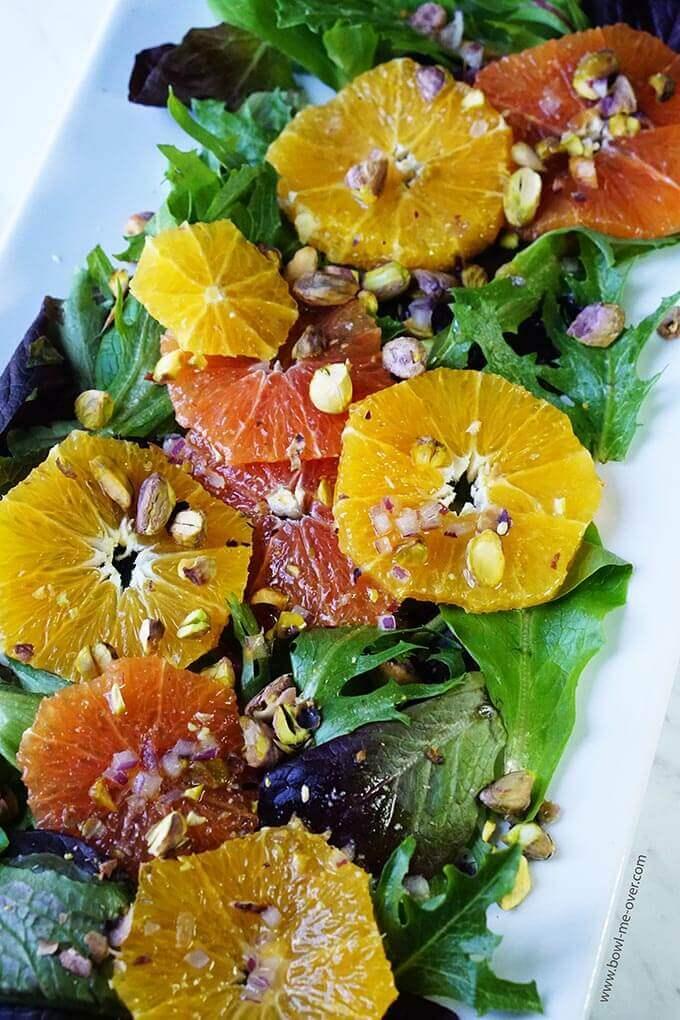 Honey Glazed Orange Salad topped with Pistachios on white platter.