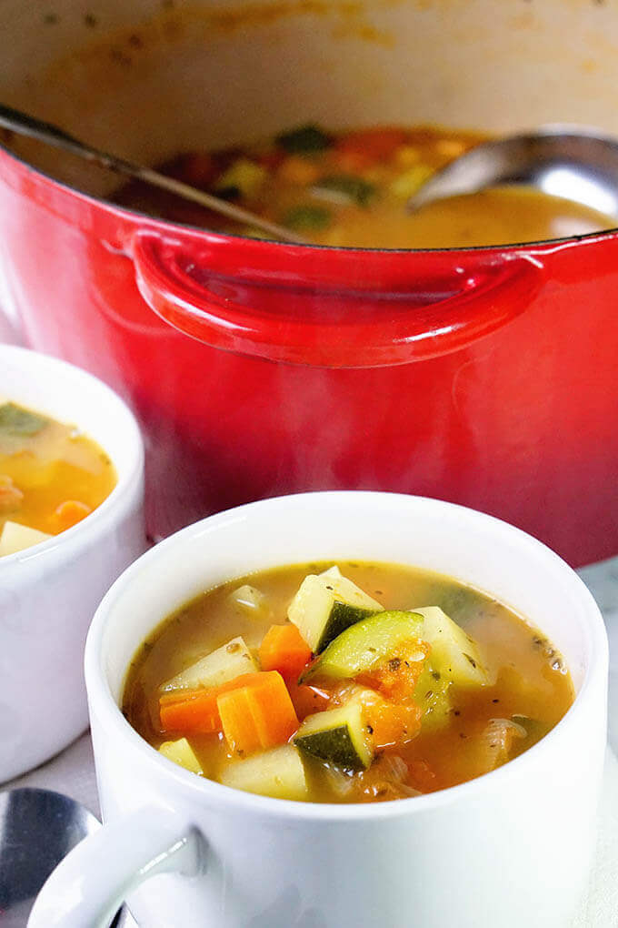 White bowls filled with vegetables tomato soup. Tomatoes, zucchini, potatoes, carrots make an amazing combination combined with roasted tomatoes!