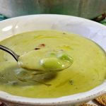 A white bowl with a spoon full of soup. This asparagus soup recipe is a so savory and creamy, but made without any cream.