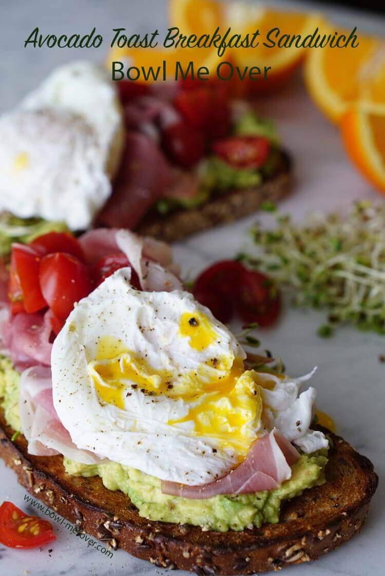 Avocado Toast - Slices of toast are sitting on a white marble counter. They are topped with mashed avocado, tomatoes, sprouts and a runny poached egg. Wedges of bright juicy oranges are in the background.