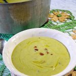 An easy asparagus soup recipe served up in a white bowl with bacon bits and a drizzle of olive oil on top.