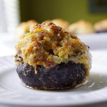 Baked stuffed mushrooms on a white plate. The top of the mushroom is golden brown and it's moist and delicious!