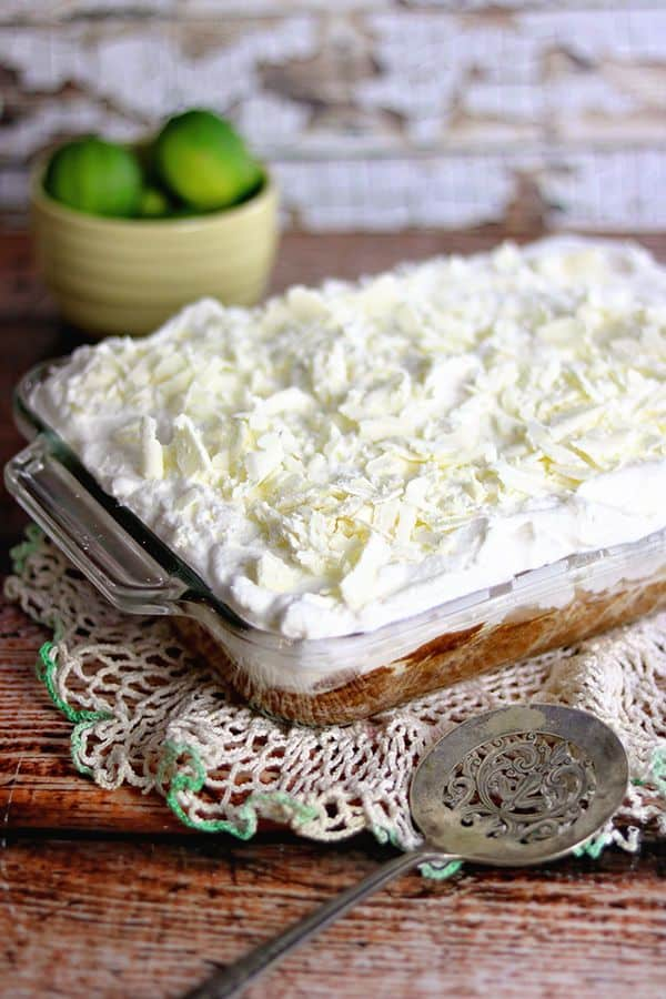 Mexican Party Food Ideas - Tres Leches Cake in glass pan topped with whipped cream.