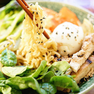 Ramen noodle bowl with soft boiled egg, chicken and vegetables with chopsticks.