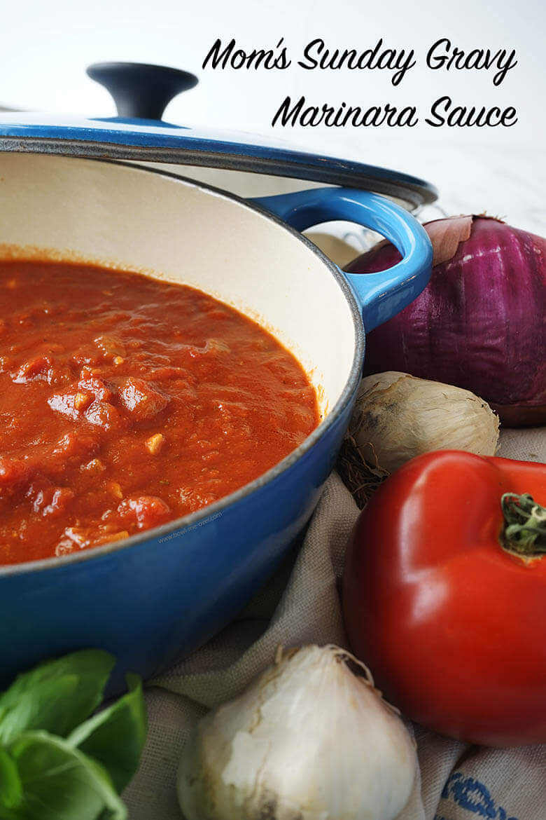 Marinara Recipe in a blue sauce pan surrounded by fresh tomatoes, garlic and onions and basil.