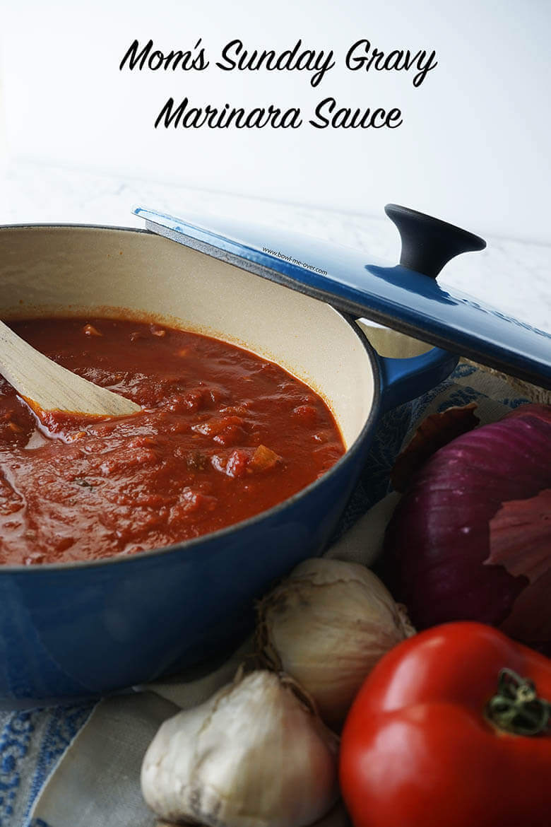 Marina recipe in a blue pot surrounded by fresh garlic, tomatoes and onions.