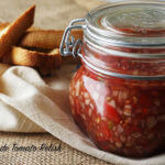 A jar of homemade tomato relish in a glass jar with toast points for serving.