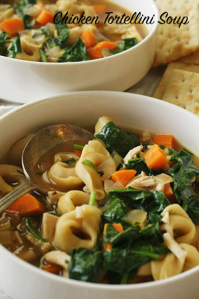 A white bowl full of soup. Cheese tortellini, spinach and carrots combine with chicken and broth for a quick and easy soup.