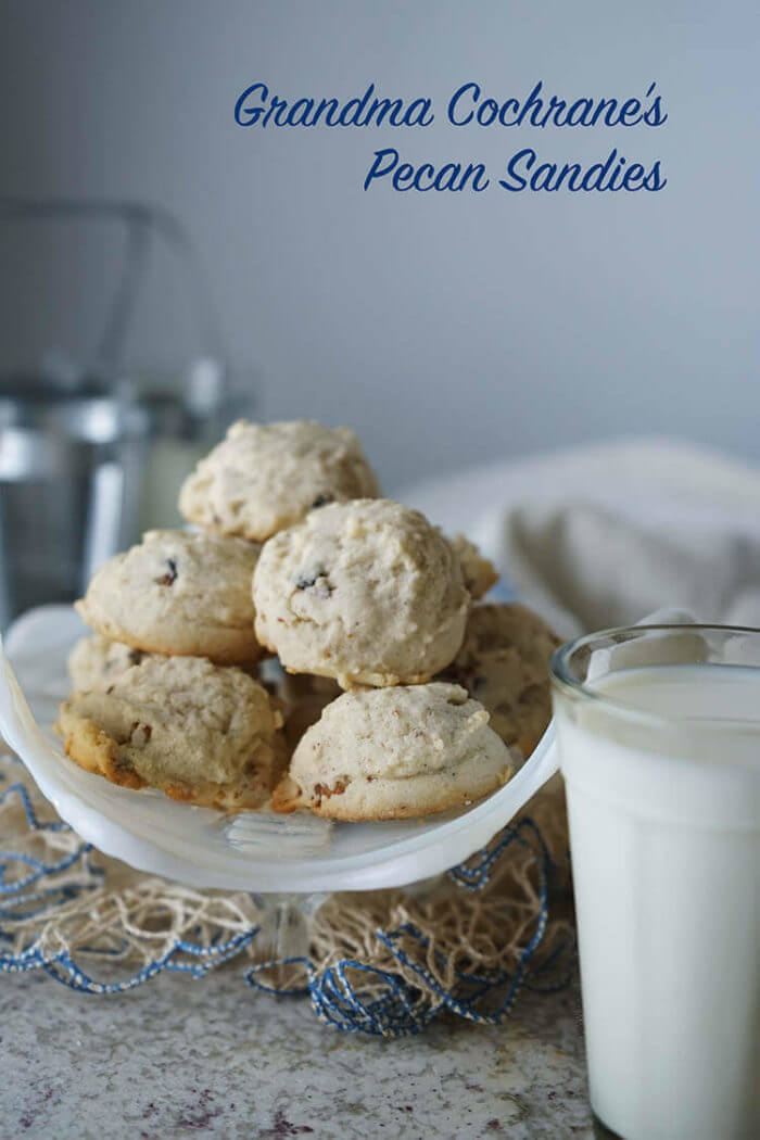 A glass of milk alongside a white bowl filled with cookies. This pecan sandies recipe had been in our family for years.