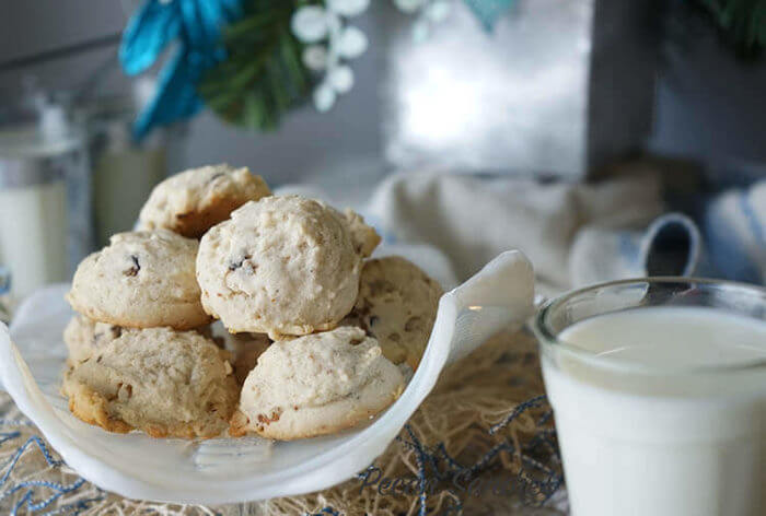 Grandma's Pecan Sandies Recipe. A while bowl filled with baked cookies and a glass of milk to dunk the cookies in!