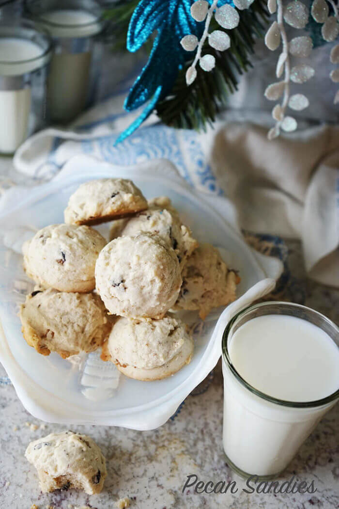 An overheat shot of perfectly baked Pecan Sandies Recipe. These cookies are golden brown and being enjoyed with a glass of milk.