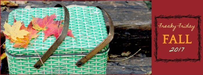 Green picnic basket with leaves on top.