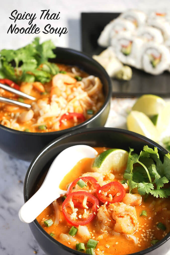 Black bowls filled with Thai Noodle Soup with Sushi on the side.