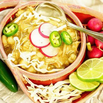 Verde chicken posole in a bowl topped with cabbage, radishes and jalapeños.
