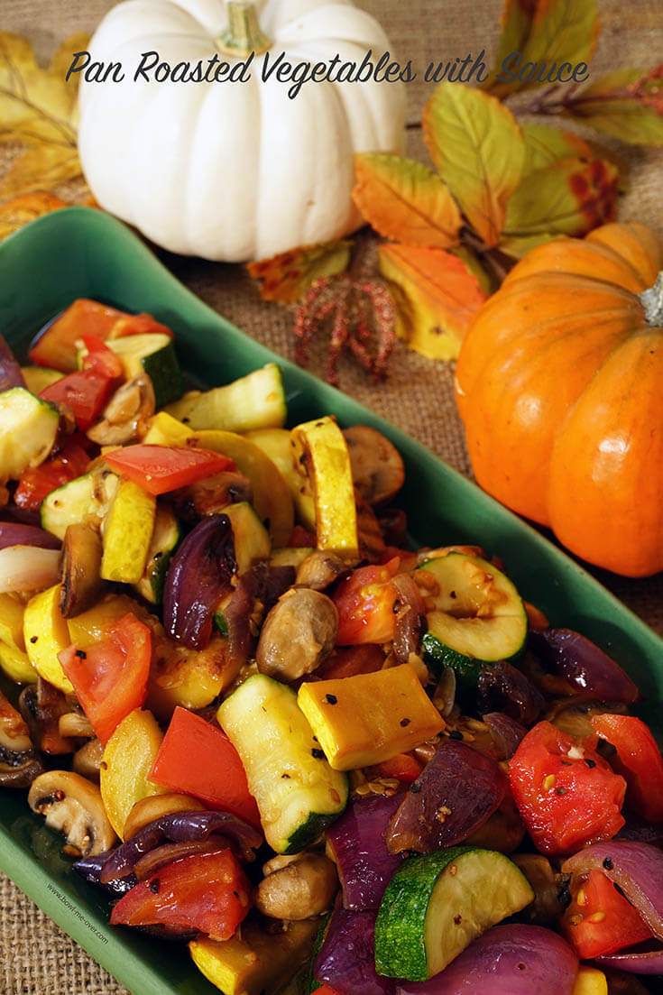 A green platter with pan roasted vegetables surrounded by beautiful fall leaves and pumpkins! A great Thanksgiving Side Dish NOT made in the oven.