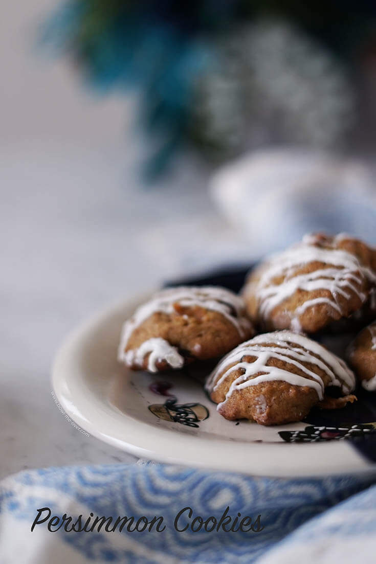 Sweet Persimmons Cookies filled with nuts, cranberries and drizzled with white chocolate on a plate.