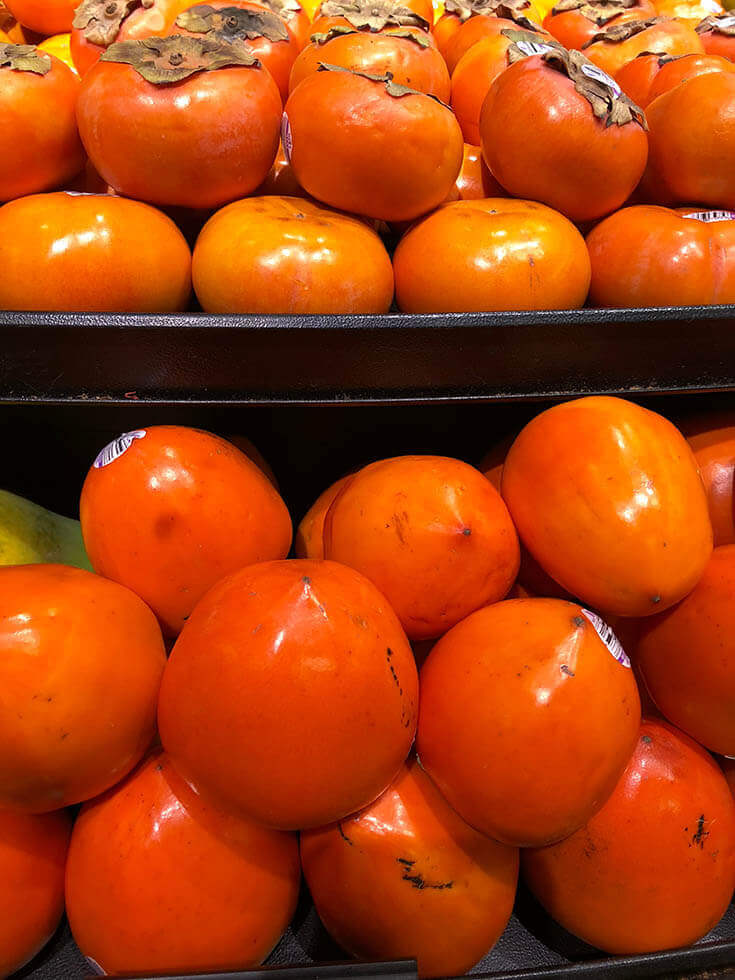 Stacks of bright orange persimmons.