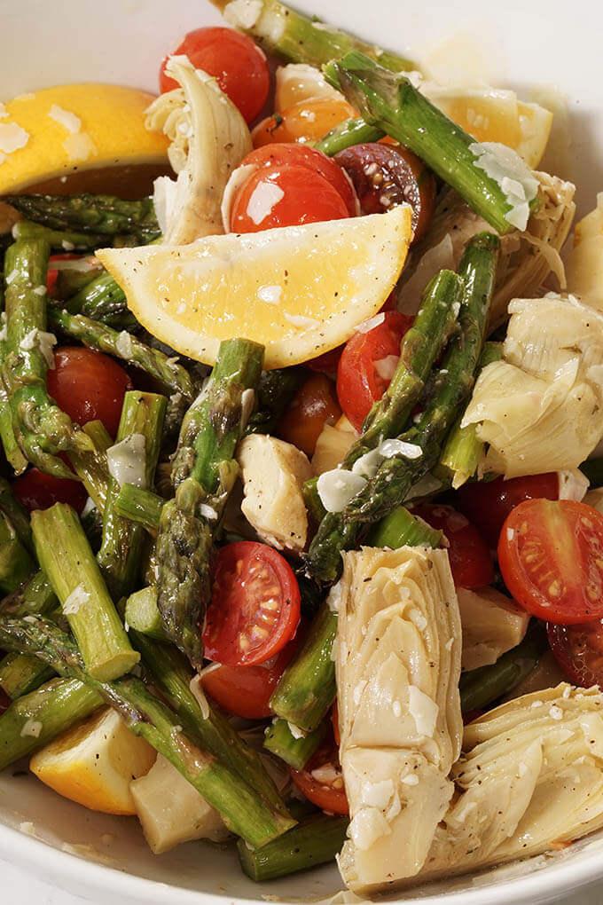 A close up picture of artichokes, tomatoes, asparagus with big juicy lemon wedges.