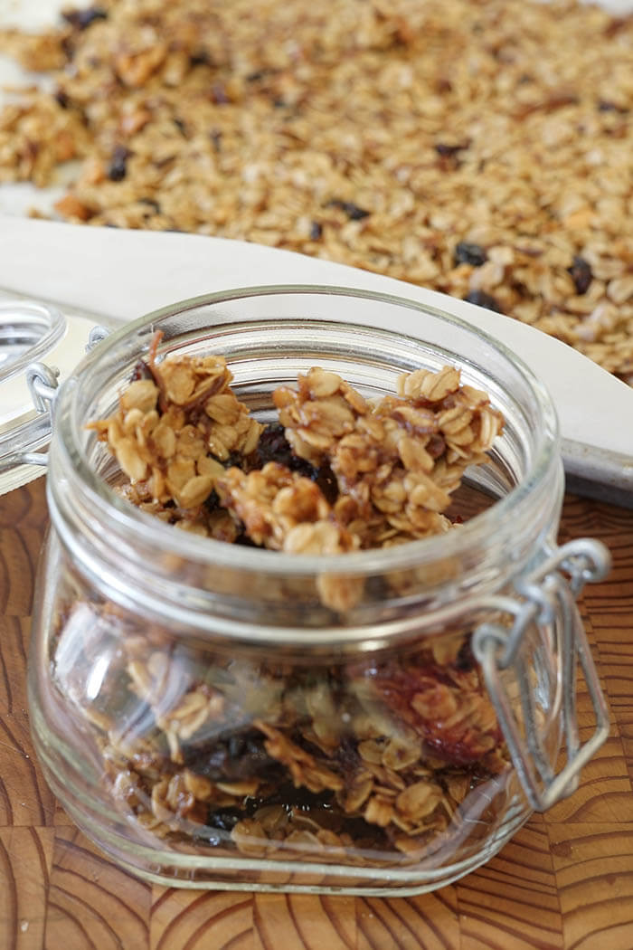 Homemade Granola Recipe - a glass jar filled with toasted homemade granola sitting on a wooden cutting board. In the background is a sheet pan filled with toasted granola fresh from the oven.