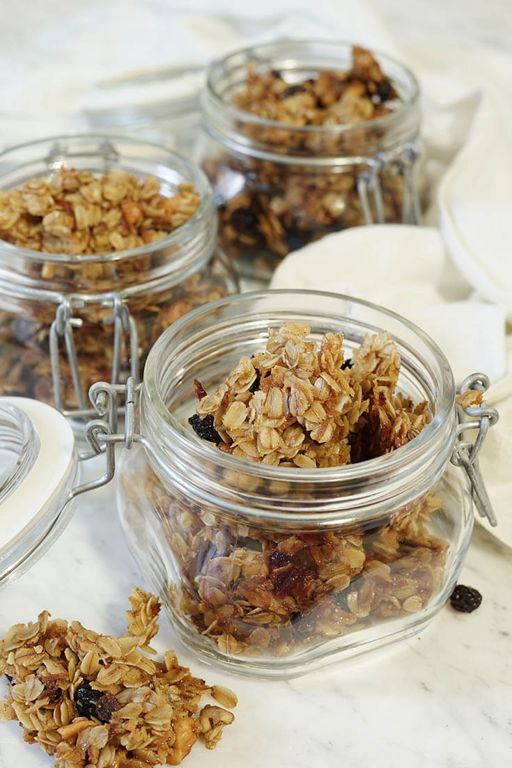 A picture of glass jars holding chunks of toasted homemade granola on a white marble slab.