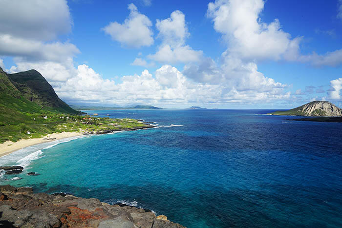 A breathtaking view from the lookout at Makapuu. High above the ocean the viewing showcases the green mountains in stark contract to the bright blue ocean. The beautiful blue sky is dotted with white puffy clouds.