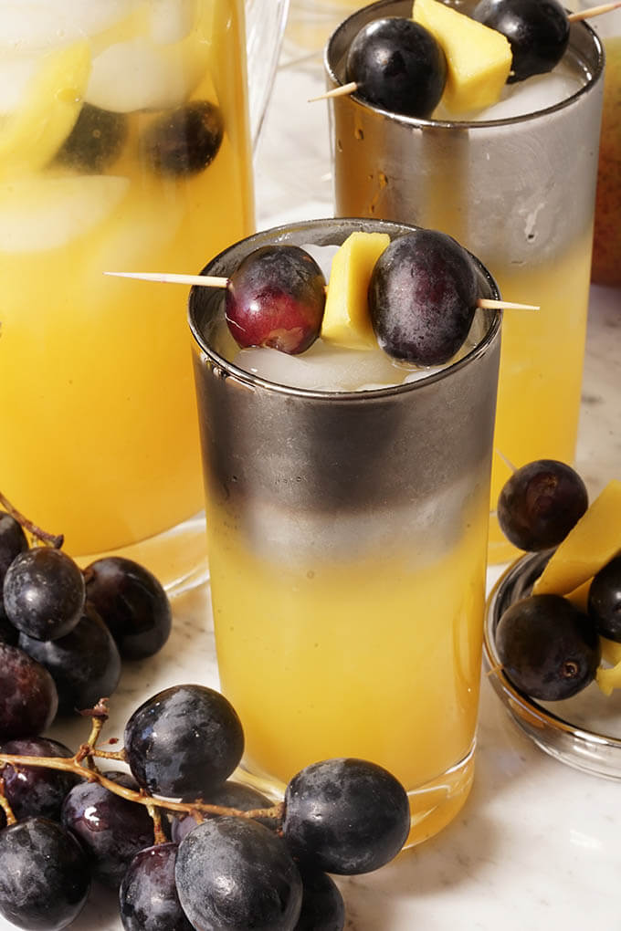 Glasses full of mango juice topped with sparkling water and garnished with grapes and chunks of mango. The glasses are surround by big purple grapes.