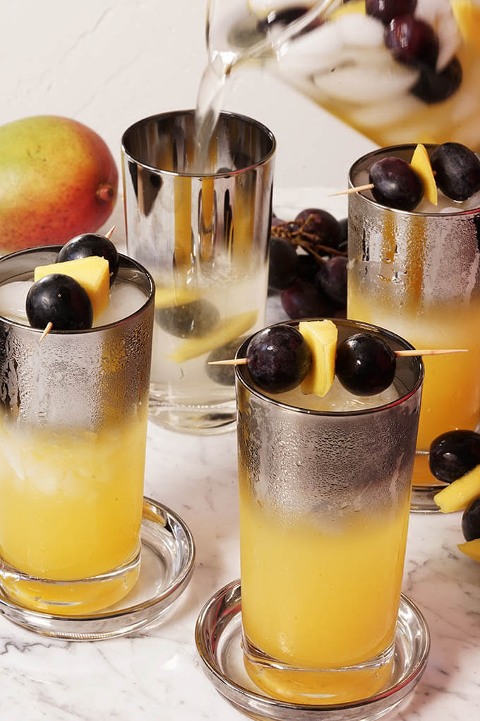 Glasses of mango juice topped off with sparkling water and garnished with grapes and mango. There are big purple grapes scattered around the drinks and a juicy ripe mango behind the glass. One glass is being filled with juice from a pitcher.