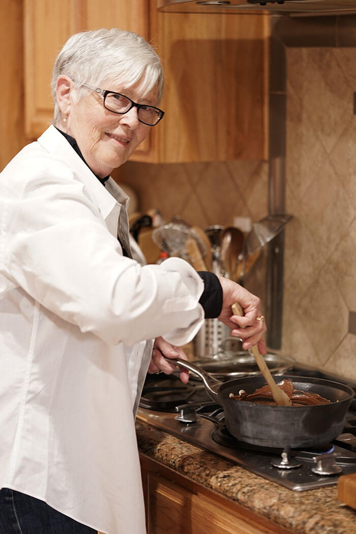 My mom is busy at the stove stirring the chocolate as it melts on the stovetop.