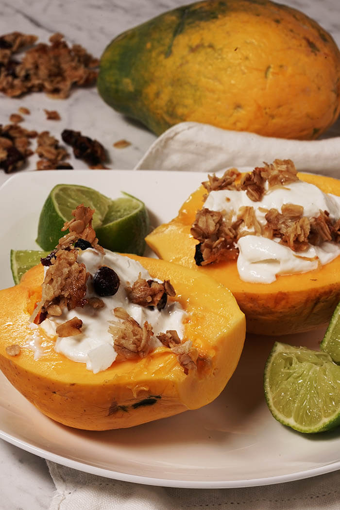 A papaya sliced in half with the seeds discarded. Each half of papaya is topped with greek yogurt and crunchy granola.