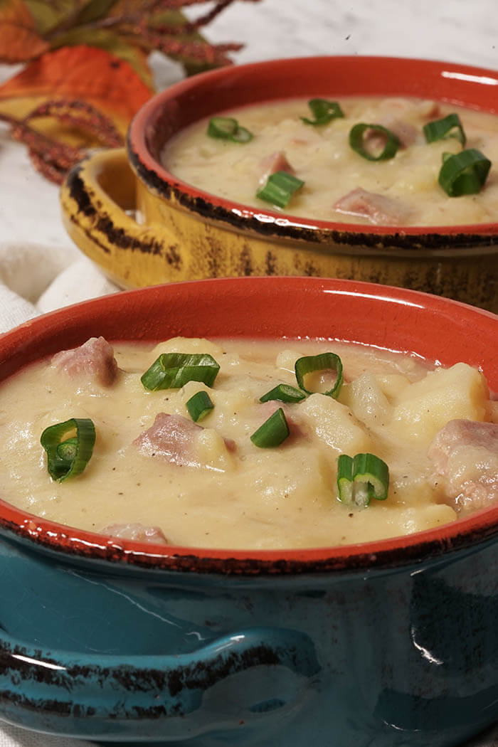 Two big hearty bowls of potato soup with ham topped with thinly sliced green onions.