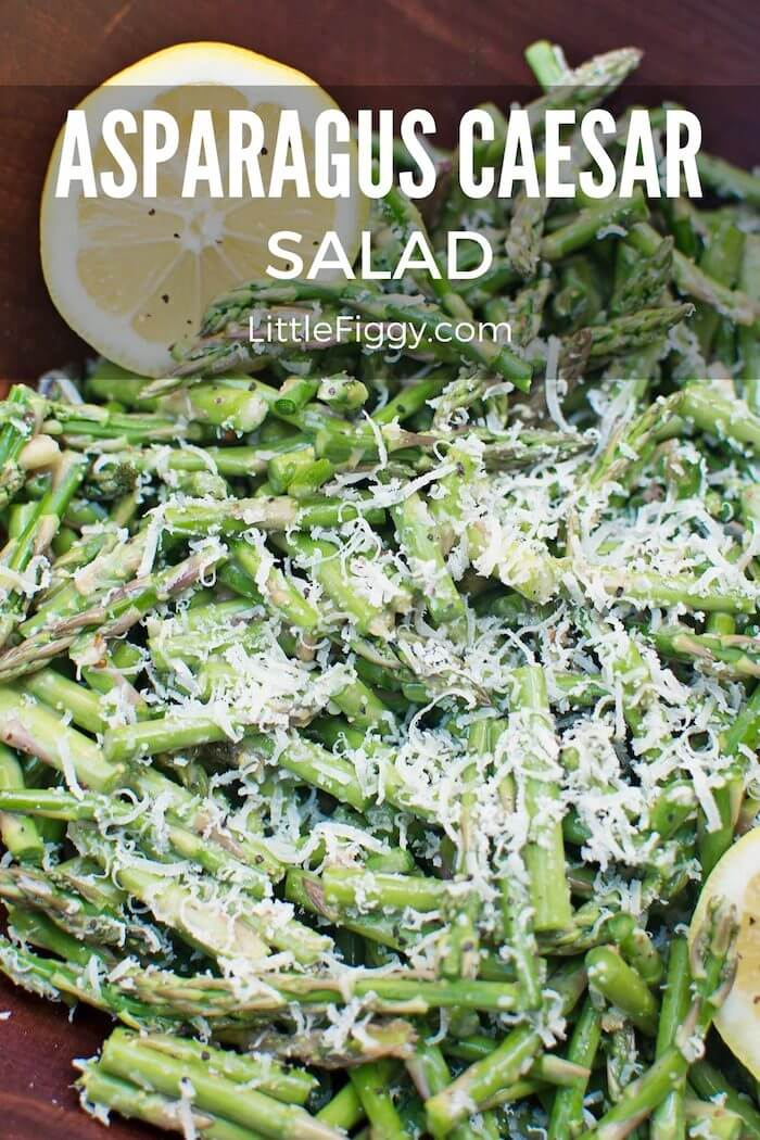 A platter piled high with asparagus Caesar salad. Grated parmesan is liberally tossed over the top and the salad is finished with bright wedges of lemons.
