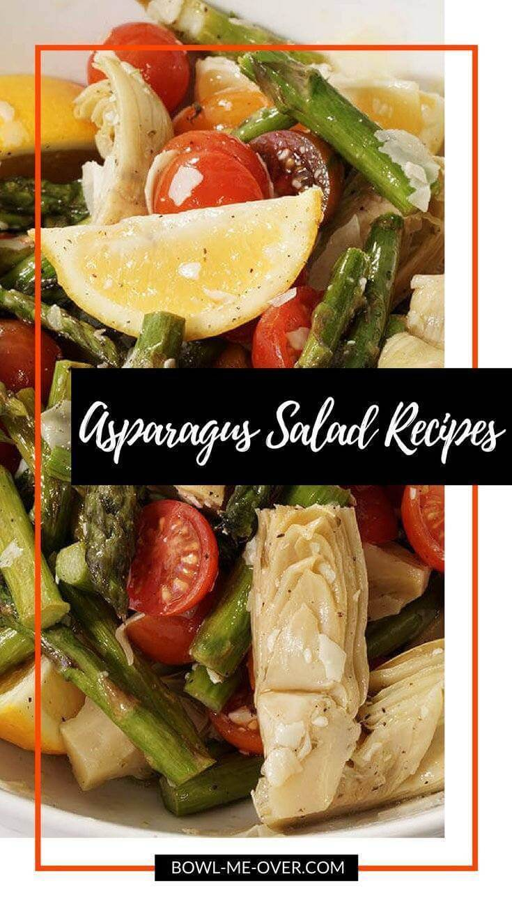 Roasted asparagus salad with wedges of lemons, sliced cherry tomatoes and marinated artichoke hearts in a large white bowl.