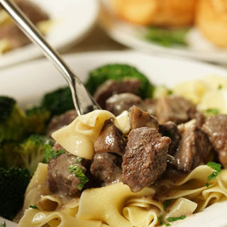 A white bowl filled with Beef Tips with Gravy served overtop noodles. A fork is digging in, ready to take a hearty bite! This meal is served with a roll and side of steamed broccoli.