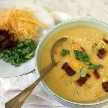 A green bowl of corn and potato chowder garnished with bacon, sliced green onions and cheese.