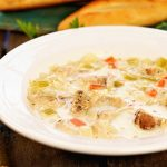 A white bowl filled with Greek Lemon Chicken Orzo Soup