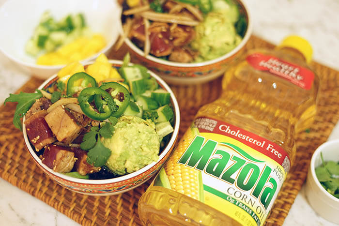 Two seared tuna poke bowl beside a container of Mazola Corn Oil.