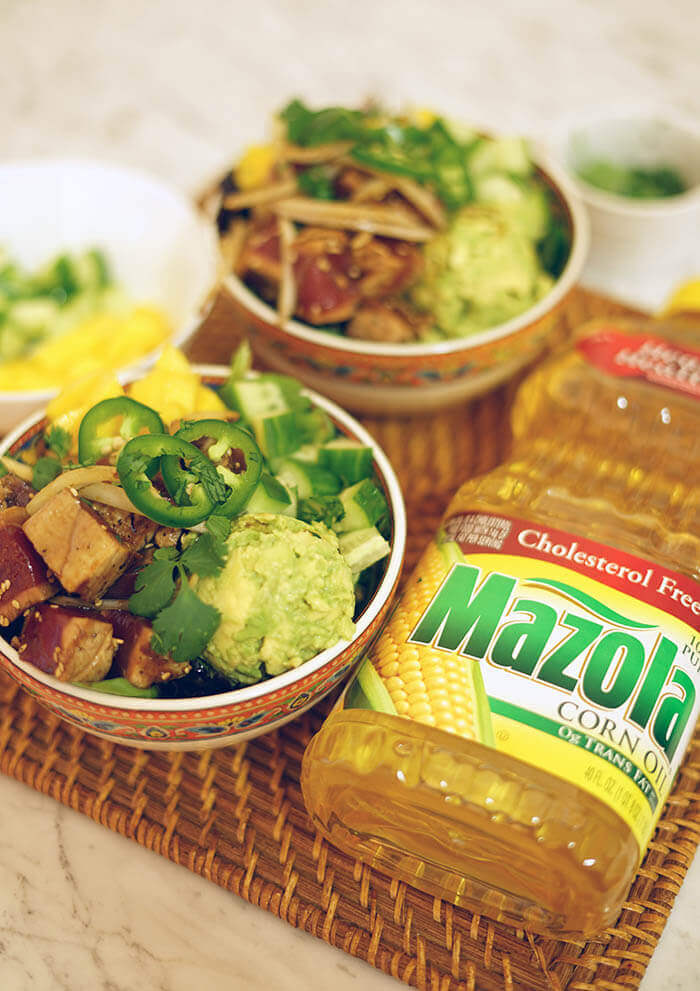 Two bowls of poke, bowls of mango and cucumber and a container of Mazola Corn Oil.