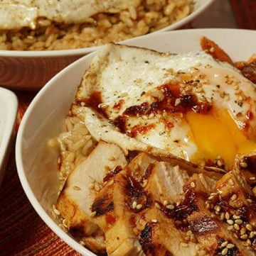 A close up of a Korean Rice Bowl with kimchi, grilled chicken marinated with a Korean BBQ Sauce Recipe and topped with a runny egg.