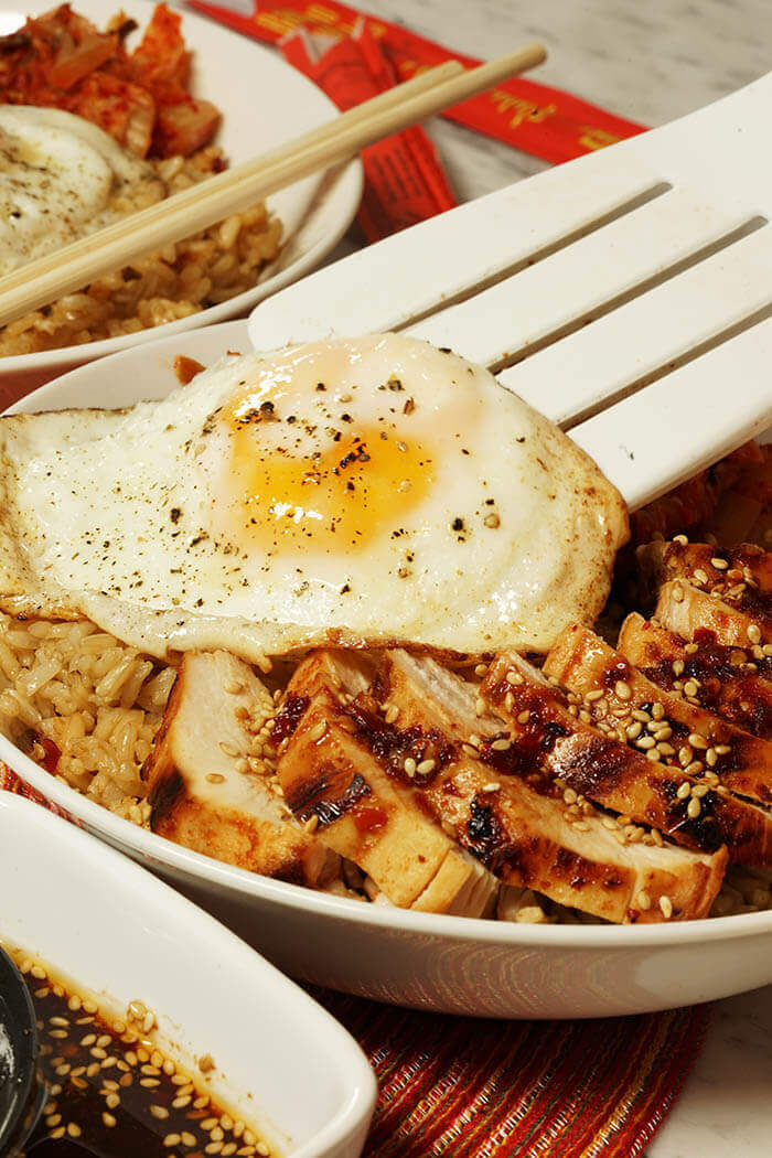 A fried egg is being placed on the rice bowl alongside thinly sliced chicken breast topped with Korean barbecue sauce.