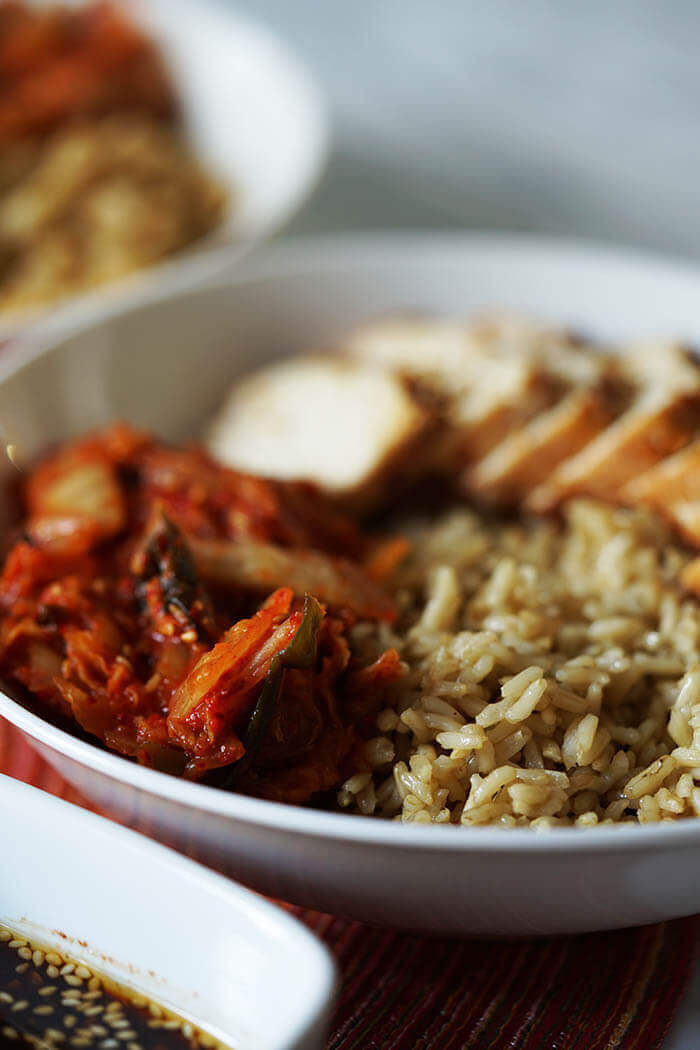 Layering this meal starts with a bowl filled with rice topped with sliced chicken breast and kimchi.