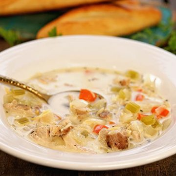 A white bowl filled with lemon chicken orzo soup served with breadsticks.