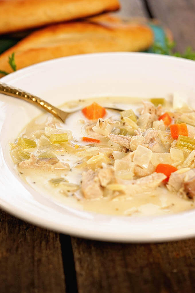 A white bowl filled with Creamy Lemon Chicken Soup Recipe with breadsticks.