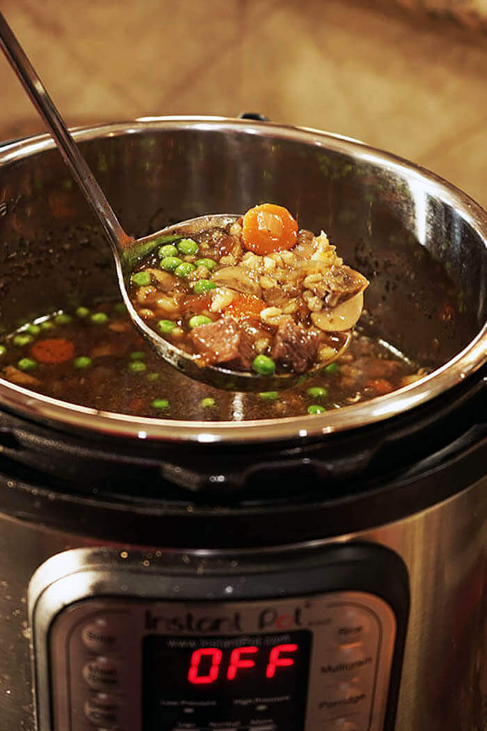 A ladle of beef barley soup being scooped out of an Instant Pot.