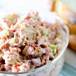 Ham Salad in a clear glass bowl with sandwiches
