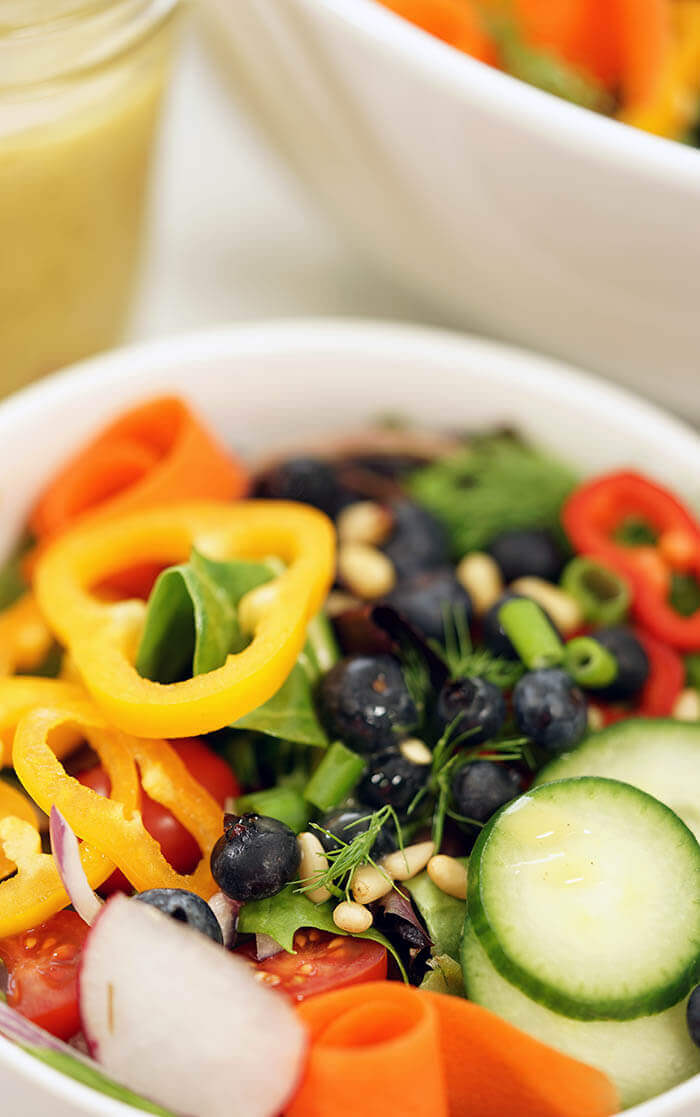 A bright crunchy garden salad recipe. The white bowl is filled with fresh vegetables, blueberries with a homemade vinaigrette on the side.