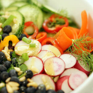 A green salad recipe with fresh vegetables, blueberries and pine nuts.