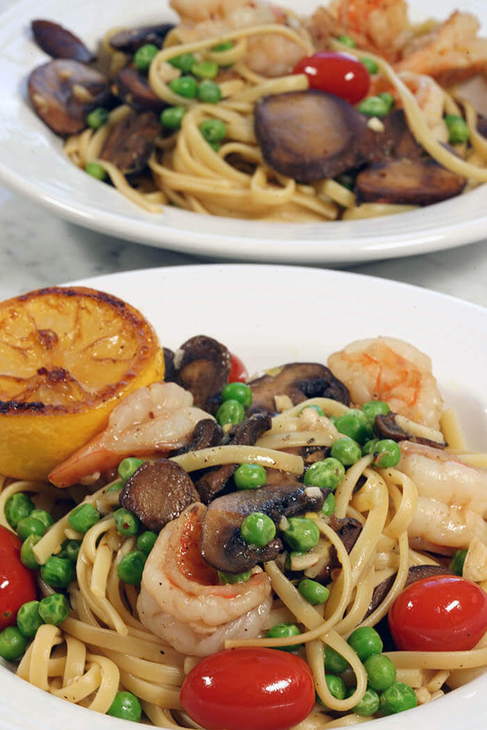 Two white bowls filled with Shrimp Scampi Linguine mixed with cherry tomatoes, sautéed mushrooms and bright green peas.