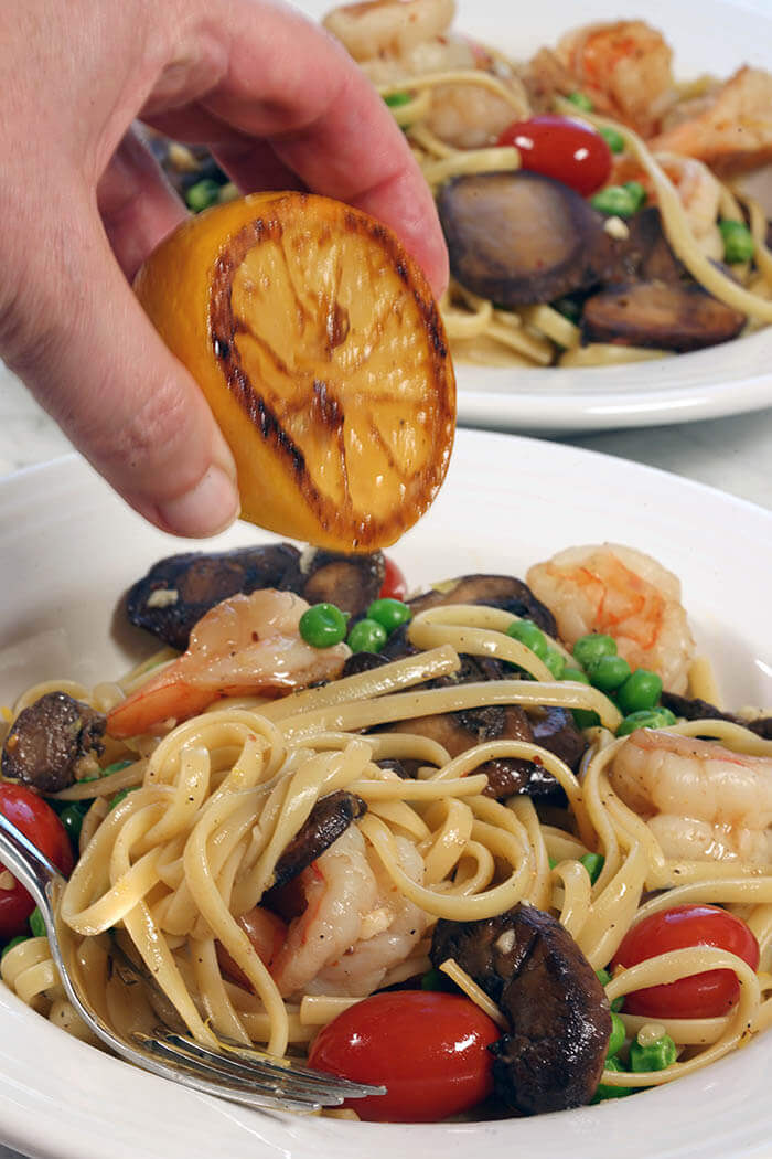 A white bowl filled with shrimp scampi linguine. The pasta is dotted with vegetables and a grilled lemon is being squeezed over the pasta.