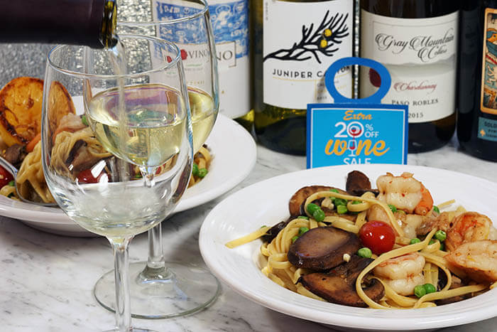 Two white bowls filled with Shrimp Scampi Linguine. There are bottles of wine to choose from and two wine glasses filled with chardonnay.