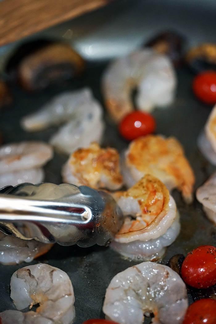 A sauté pan filled with mushrooms, tomatoes and golden sautéed shrimp.